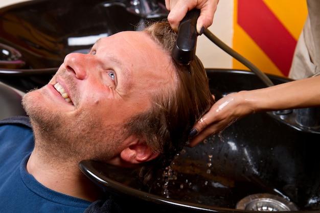Lavar o cabelo do homem no salão de cabeleireiro salão de beleza Foto Premium