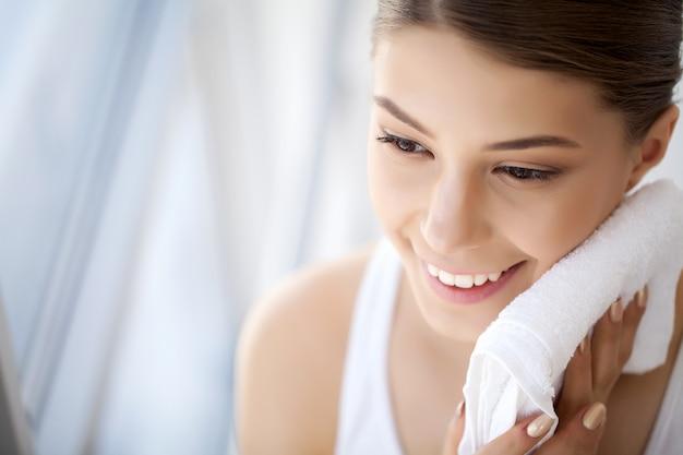 Lavar o rosto, close da mulher feliz secar a pele com toalha Foto Premium