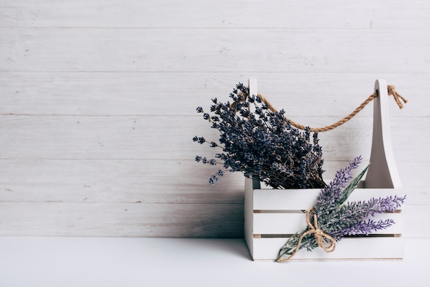 Lavenders na caixa de madeira branca contra o pano de fundo de madeira Foto gratuita
