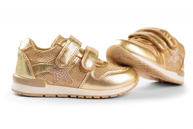 Lay plana. calçado desportivo infantil ouro isolado no branco Foto Premium