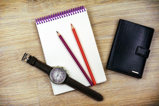 Lay plana. relógio de pulso masculino, bloco de notas, dois lápis e uma carteira masculina se debruçam sobre a textura da madeira Foto Premium