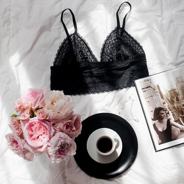 Lay plana. vista superior lingerie de renda preta, buquê de rosas e pions, café na ba cama branca Foto Premium