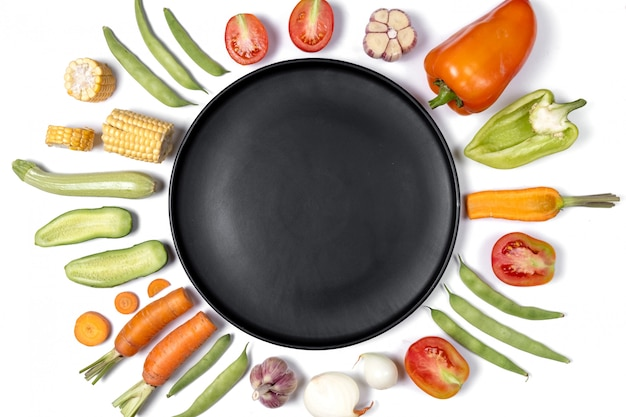 Layout criativo feito de haricot, tomate, pimenta, cenoura, alho, milho, abobrinha, cebola e chapa preta. Foto Premium