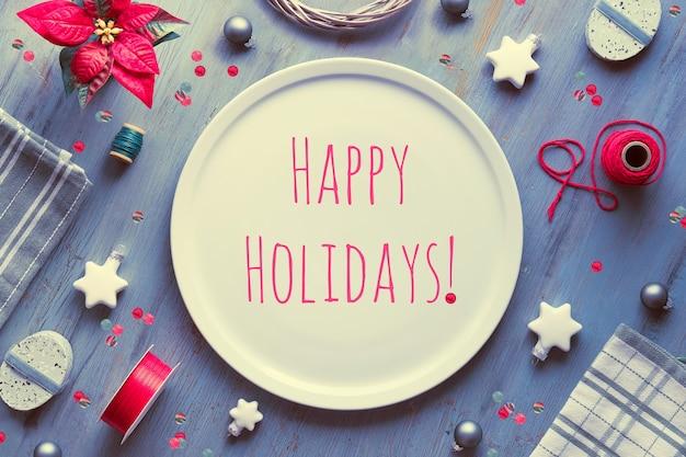 Layout da mesa de natal. vista superior em madeira texturizada cinza, camada plana geométrica, arranjo com poinsétia vermelha, estrelas brancas, tecido Foto Premium