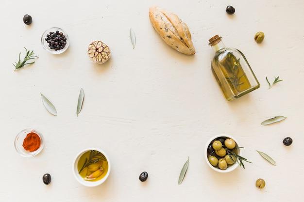 Layout de azeitonas de pão de garrafa de óleo e especiarias Foto gratuita