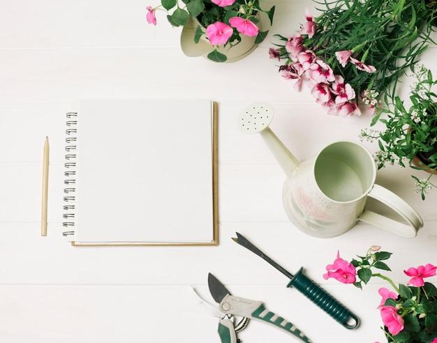 Layout de flores e bloco de notas Foto gratuita
