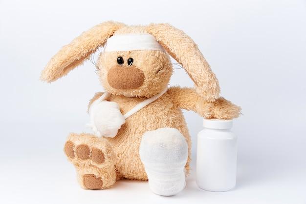 Lebre enfaixado doente bonito com um frasco das medicinas em um fundo branco. Foto Premium