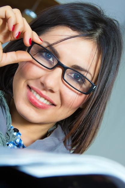 Leer revista morena gafas elegante Foto Premium