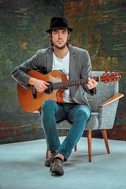 Legal cara com chapéu tocando violão no espaço cinza Foto gratuita
