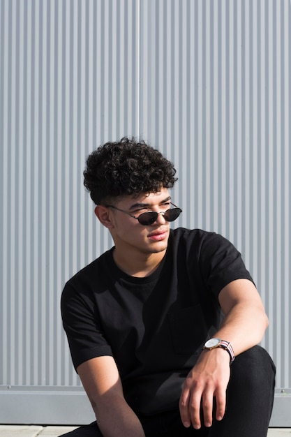 Legal cara negro com cabelo encaracolado em óculos de sol Foto gratuita