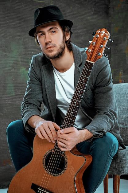 Legal cara sentado com guitarra no espaço cinza Foto gratuita