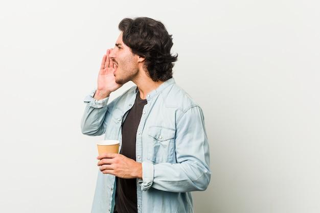 Legal jovem bebendo um café, gritando e segurando a palma da mão perto da boca aberta. Foto Premium