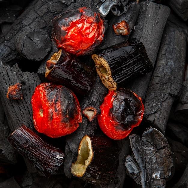 Legumes assados de tomate e berinjela em carvão, plana leigos. Foto gratuita
