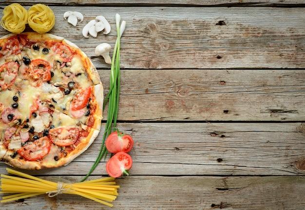Legumes, cogumelos e tomates pizza em um fundo de madeira Foto Premium