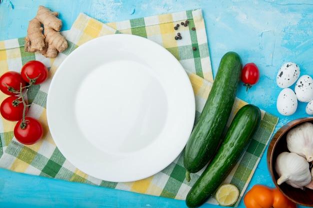 Legumes com prato vazio no pano na mesa azul Foto gratuita