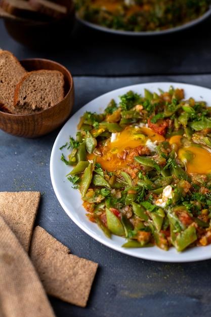 Legumes cozidos coloridos diferentes, juntamente com pão na mesa cinza Foto gratuita