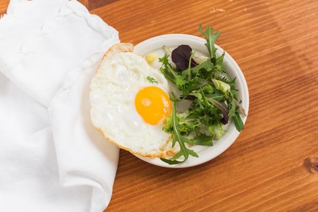 Legumes e metade de ovos fritos na chapa sobre a mesa de madeira Foto gratuita