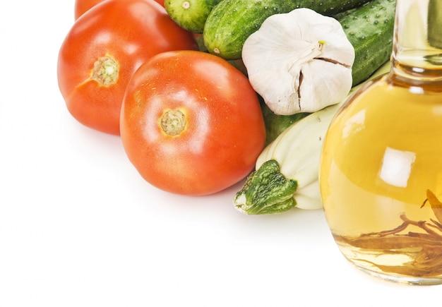 Legumes e uma garrafa de óleo, ainda vida isolada no fundo branco Foto Premium