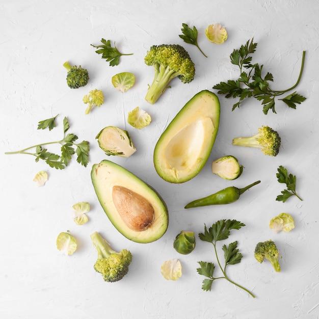 Legumes em fundo branco com abacate no centro Foto gratuita