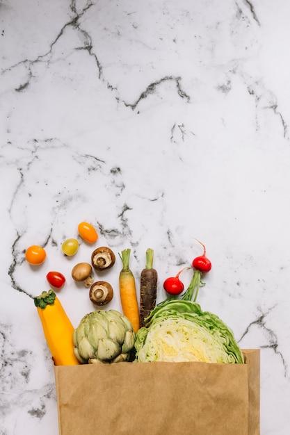 Legumes em saco de compras contra o fundo de mármore branco Foto gratuita