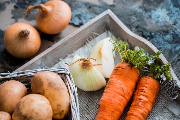Legumes em uma cesta: beterraba, cebola, alho, endro, batatas, cenouras em um fundo de madeira velha Foto Premium
