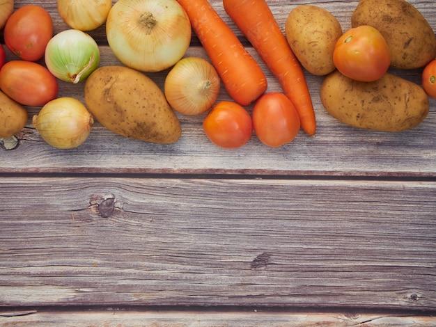 Legumes frescos, cebolas, tomates, cenouras, batatas, colocados em uma mesa de madeira, vista de cima Foto Premium