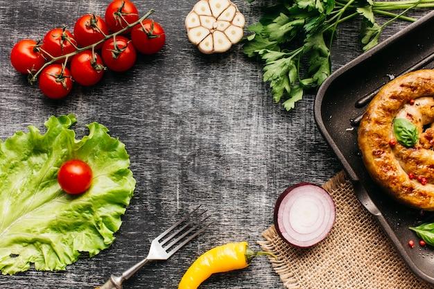 Legumes frescos e salsicha de caracol grelhados dispostos em moldura circular Foto gratuita