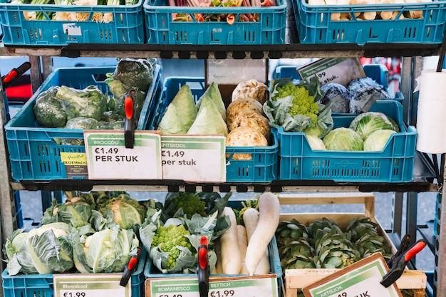Legumes frescos em caixas azuis na prateleira com etiqueta de preço Foto gratuita