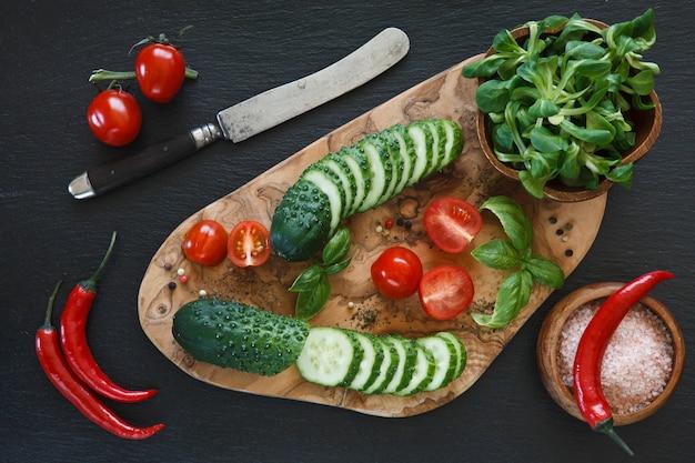 Legumes frescos na tábua de madeira com faca em fundo preto concreted Foto Premium