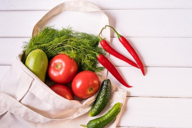 Legumes frescos no saco de compras desperdício zero reusável de matéria têxtil do eco sobre o fundo branco, orientação horizontal. Foto Premium