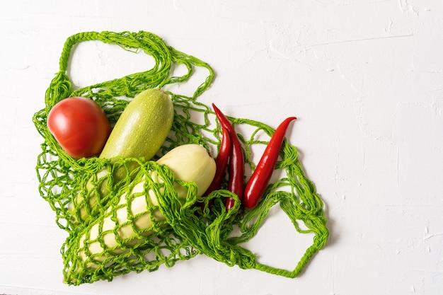 Legumes frescos no saco de compras reusável da malha do desperdício zero do eco sobre o fundo branco, orientação horizontal. Foto Premium