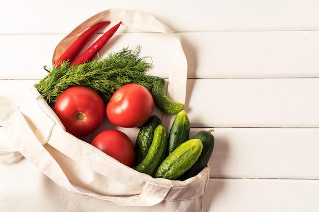 Legumes frescos no saco de compras waste reusável da matéria têxtil do eco zero sobre o fundo branco, orientação horizontal. Foto Premium