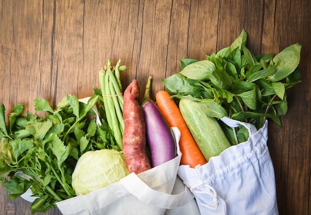 Legumes frescos orgânicos em sacos de tecido de algodão ecológico na mesa de madeira Foto Premium