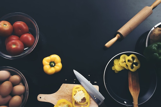Legumes frescos, ovos e pimento de pimentão no fundo de madeira preto. Foto gratuita