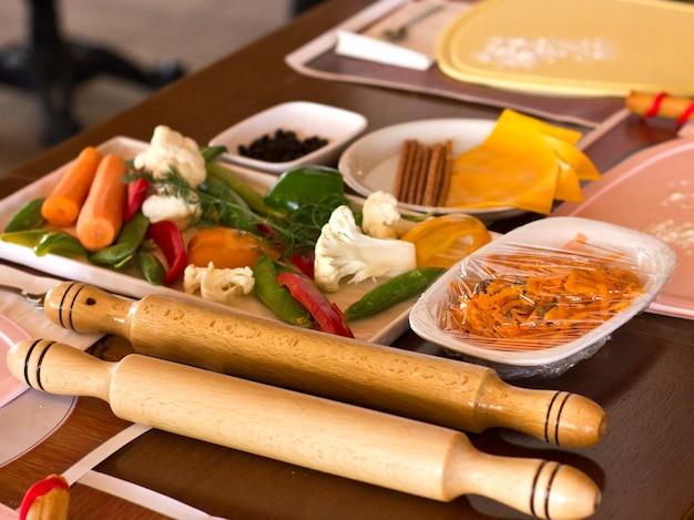 Legumes frescos, queijo e rolo de madeira. loja de trabalho de cozinha Foto Premium