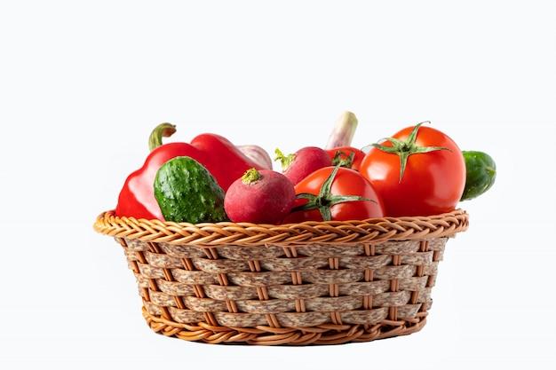 Legumes frescos sortidos em uma cesta em um fundo branco. conceito de comida ecológica. Foto Premium