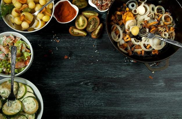 Legumes . molho de abobrinha frito em um prato. jovens batatas cozidas com endro em uma tigela. cogumelos chanterelle fritos com cebolas douradas em uma frigideira. copyspace Foto Premium