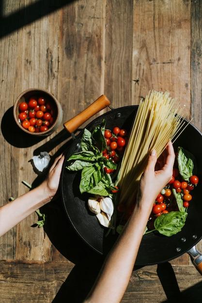 Legumes orgânicos frescos e ingredientes preparados em uma panela Foto Premium