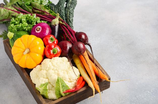 Legumes orgânicos frescos em caixa de madeira no fundo cinza concreto. Foto Premium