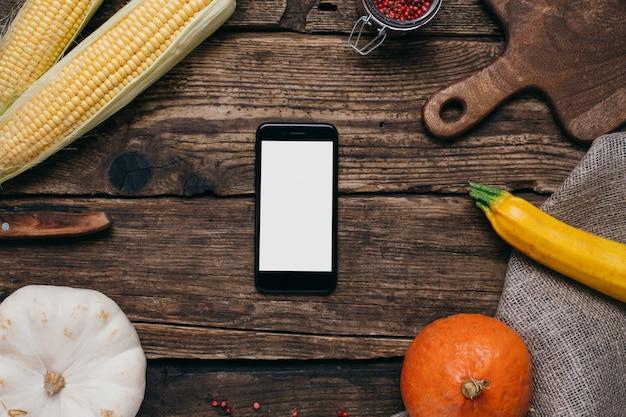 Legumes outono: telefone móvel, com, branca, vazio, tela, abóboras, e, milho, com, amarela sai, ligado, madeira Foto Premium