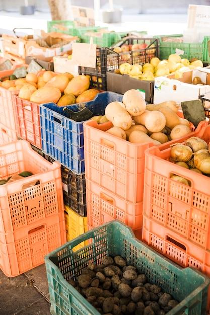 Legumes produzem em caixas plásticas no mercado local Foto gratuita