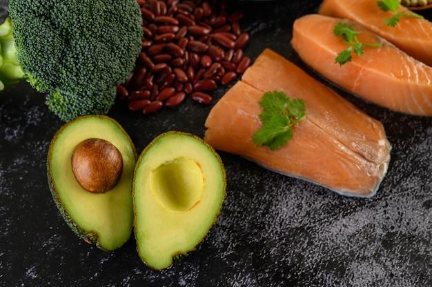 Leguminosas, brócolis, frutas e salmão colocados sobre um piso de cimento preto. Foto gratuita