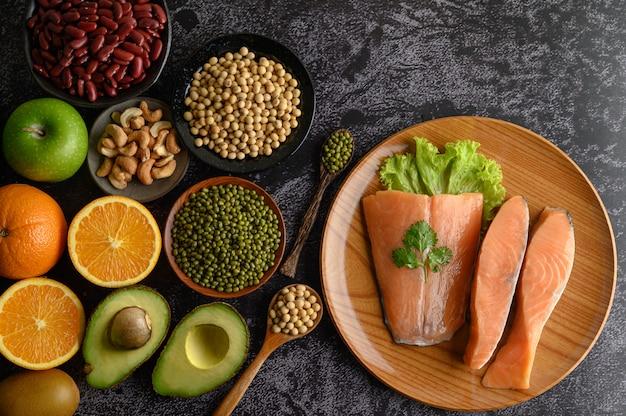 Leguminosas, frutas e pedaços de salmão em uma placa de madeira. Foto gratuita