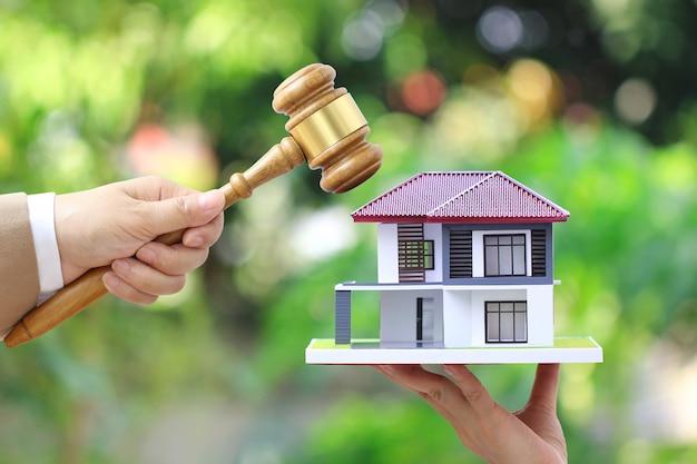 Leilão de propriedade, mão de mulher segurando o martelo de madeira e casa modelo em branco Foto Premium