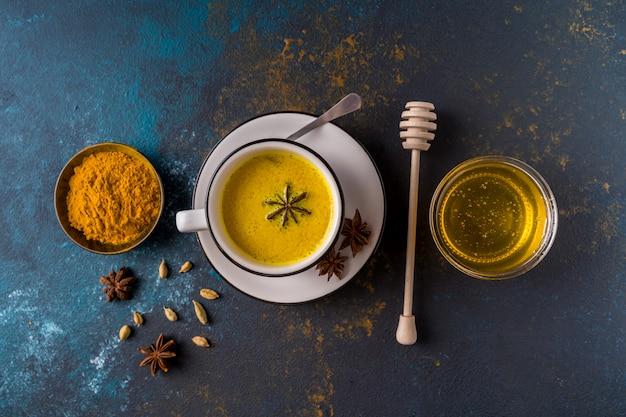 Leite açafrão ayurvédico dourado com leite feito com açafrão e outras especiarias na superfície azul Foto Premium