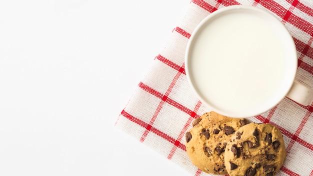 Leite com biscoitos no guardanapo sobre o fundo branco Foto gratuita