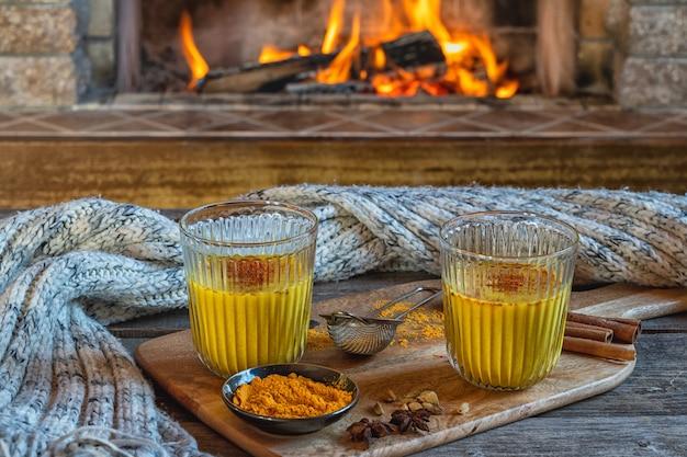 Leite com leite dourado em dois copos com açafrão e especiarias antes da lareira. Foto Premium