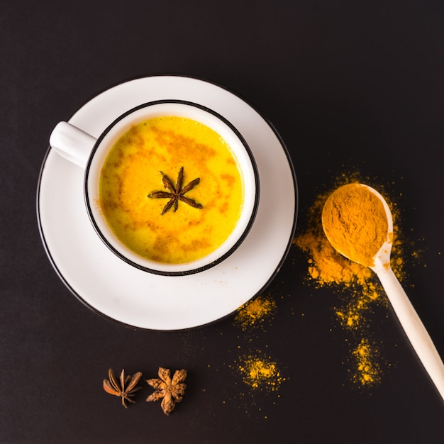 Leite de açafrão dourado com leite com curcuma em um copo grande sobre fundo preto. Foto Premium