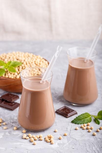 Leite de chocolate orgânico da soja não lácteos na placa de vidro e de madeira com feijões de soja em um fundo concreto cinzento. Foto Premium