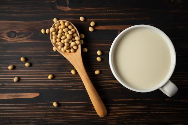 Leite de soja e feijão de soja na mesa de madeira. Foto gratuita